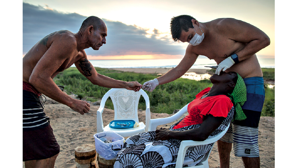 Os dentistas brasileiros Sergio Torres (à esq.) e Fábio Araki atendem uma moradora de Catanas Point, em um consultório improvisado na praia