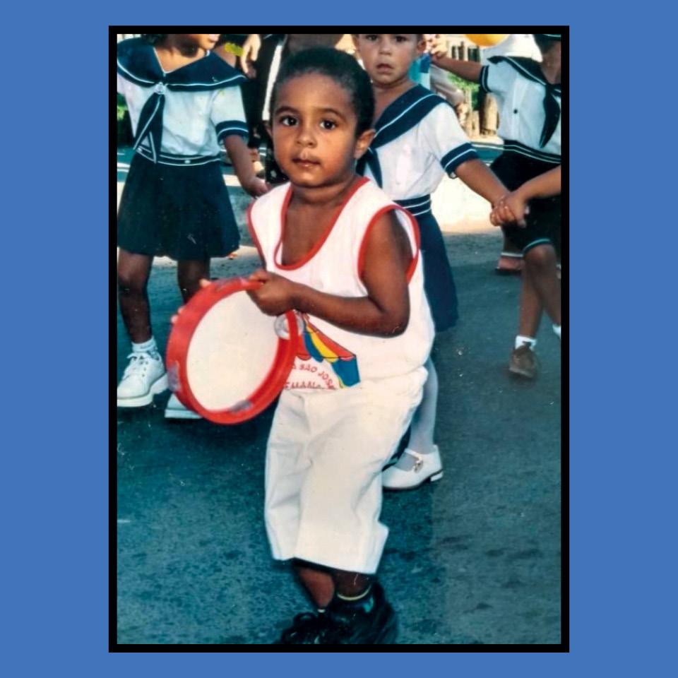 Baco, aos 4 anos, tocando pandeiro em festa na escola
