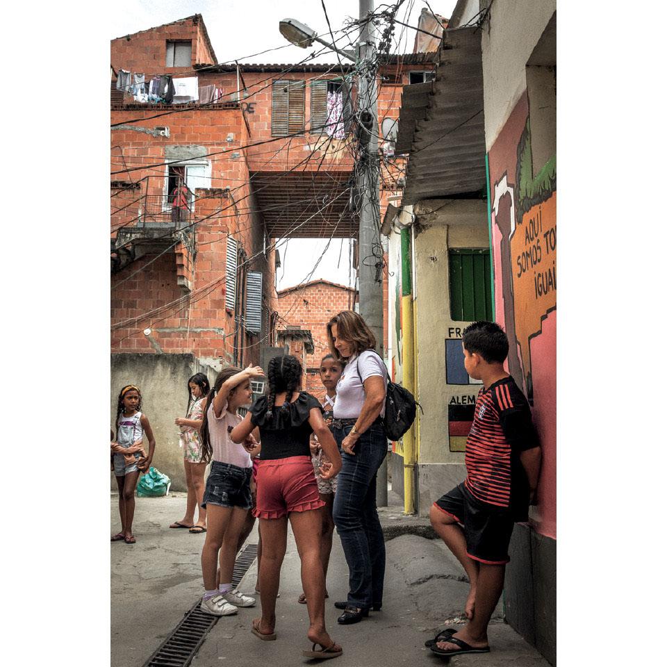 Yvonne conversa com crianças no Complexo do Alemão, onde mantém o projeto Uerê