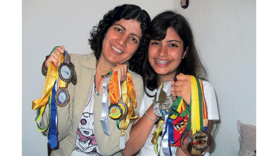 Com a mãe, Reni, e as medalhas conquistadas em olimpíadas de ciência e matemática em 2011