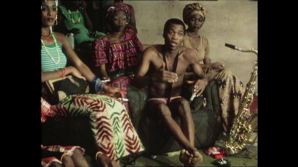 Fela sentado em volta de algumas de suas esposas