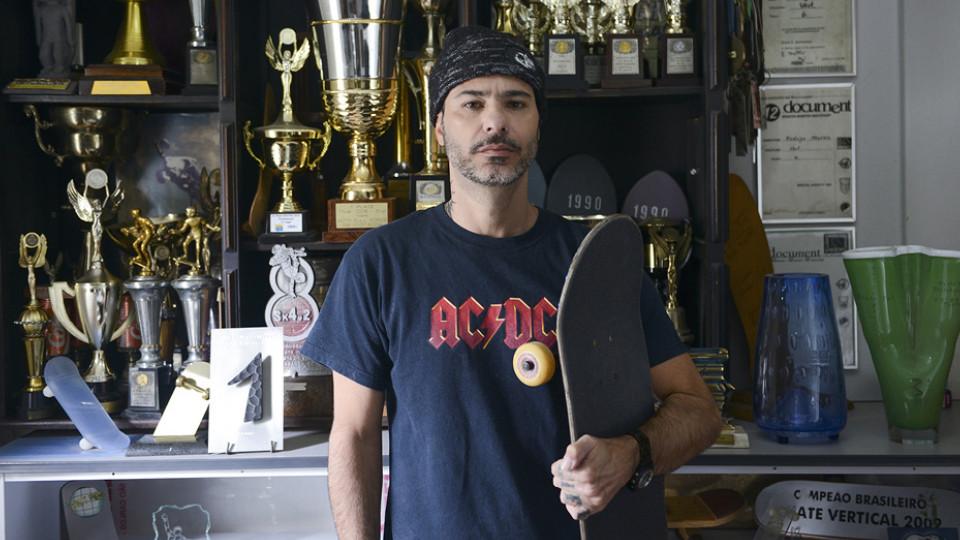 Digo Menezes à frente de alguns dos troféus que guarda em sua casa, em São Paulo