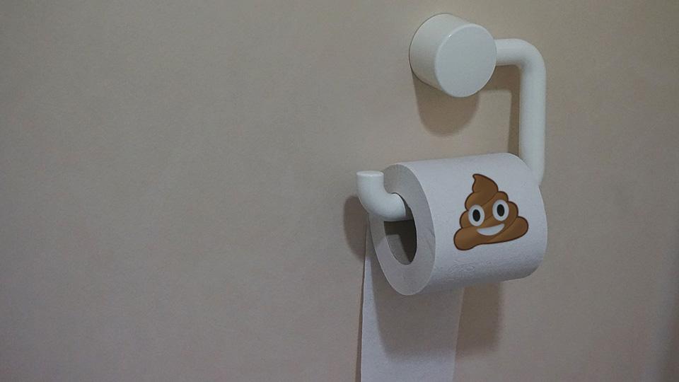 Rolo de papel higiênico com emoji do cocô feliz e sorridente