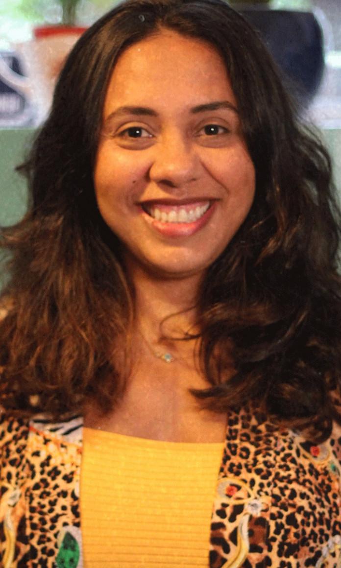 Com os cabelos soltos e uma blusa amarela, a jornalista Fabiane Pereira sorri para a foto