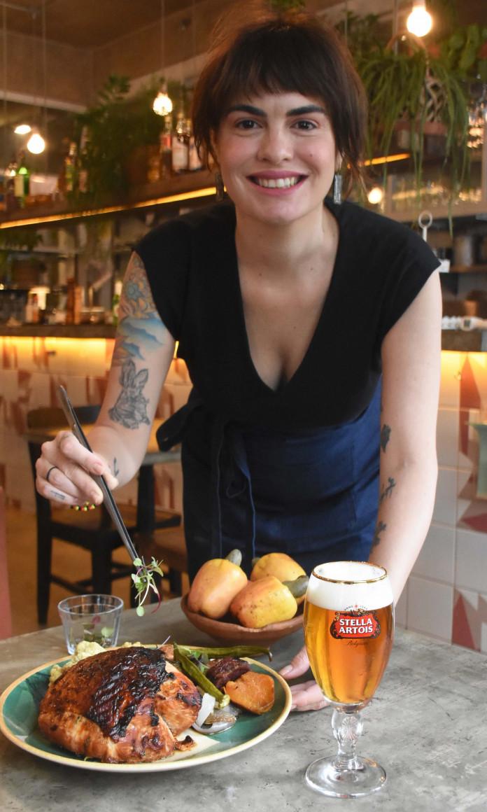 A chef Cafira Foz, de cabelos pretos e franja, sorri sobre a mesa servida em seu restaurante, o Fitó