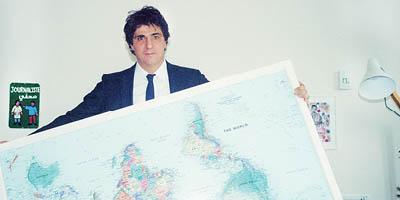 Guga Chacra segurando um mapa de ponta cabeça com a mão em casa