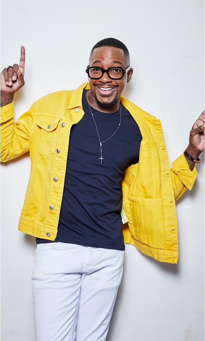 De casaco amarelo e camiseta azul, o cantor, ator e apresentador Mumuzinho está com as mãos para cima