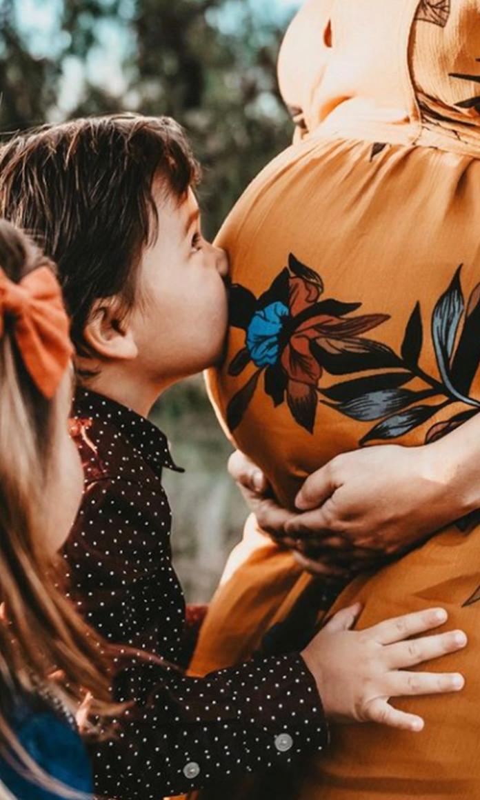 Crianças beija a barriga da mãe, que está em pé e usa um vestido laranja