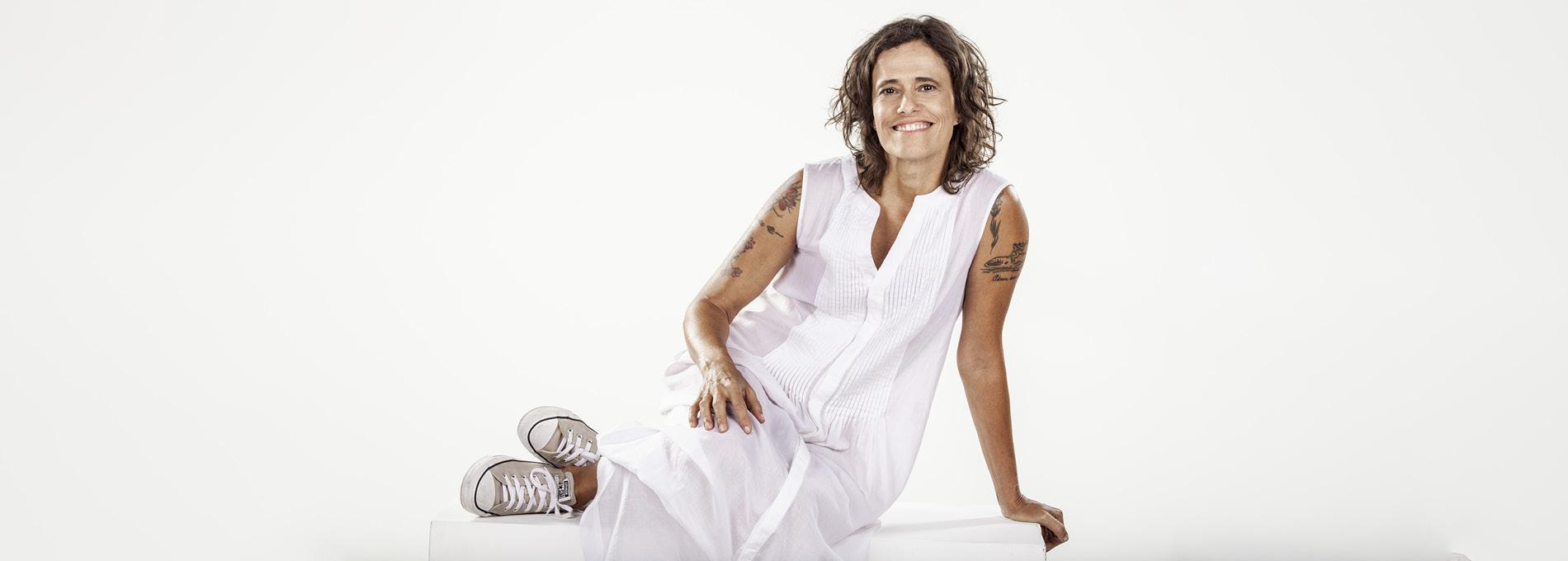 Zélia Duncan de branco fundo branco sentada
