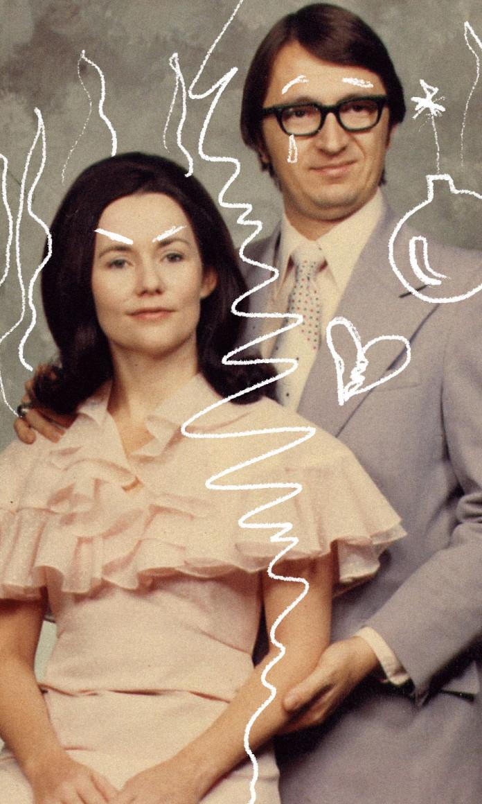 Casal vestido com roupas sociais se abraça para a foto, decorada com rabiscos de bomba indicando uma crise