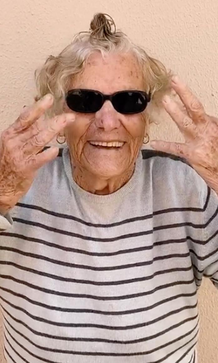 Vó Rosalina, influenciadora e tiktoker, usa óculos escuros, camiseta listrada e faz uma gracinha com as mãos ao lado do rosto