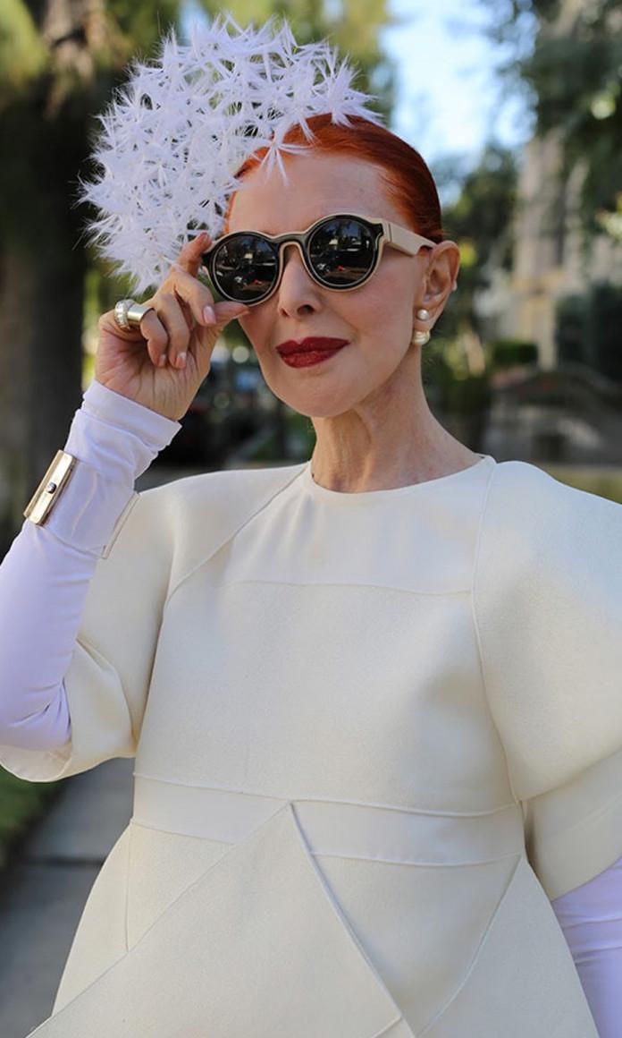 Senhora ruiva veste um vestido branco de alta costura, segura os óculos escuros com as mãos e tem um adereço de penas na cabeça