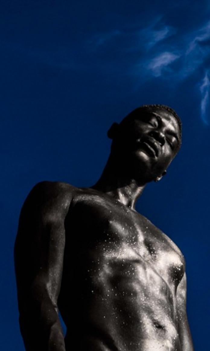 À frente de um céu azul, homem negro está em pé de olhos fechados, foto que faz parte do projeto Black Is Beautiful