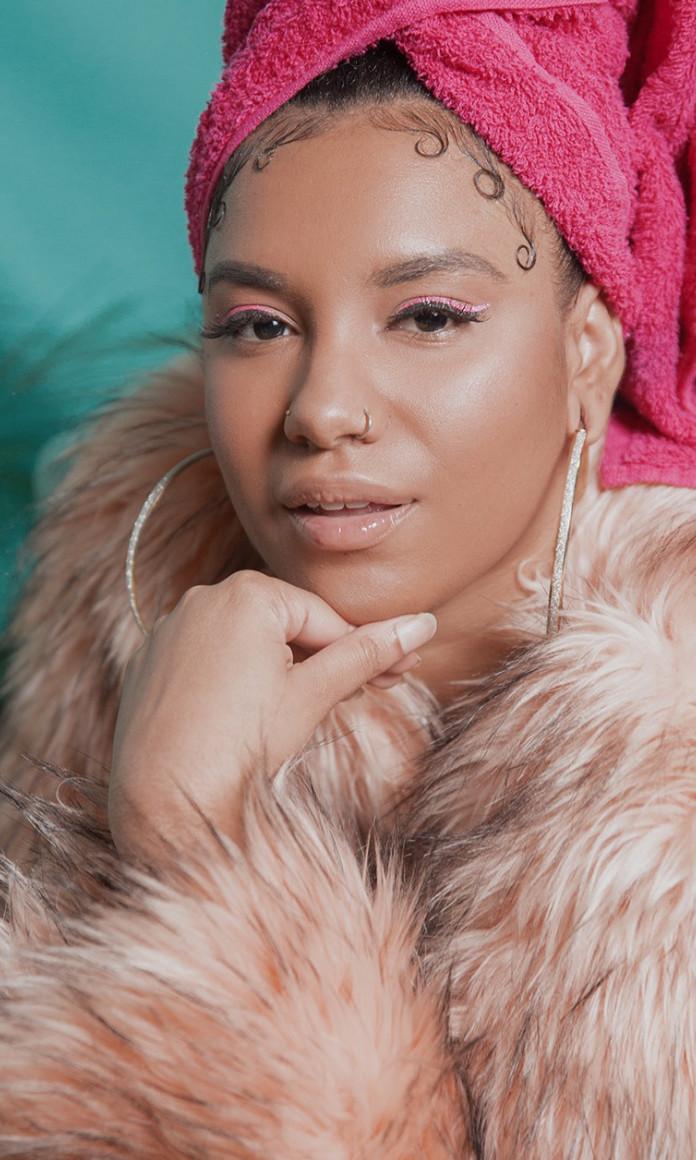 mulher negra de toalha rosa na cabeça, argolas e casaco de pele