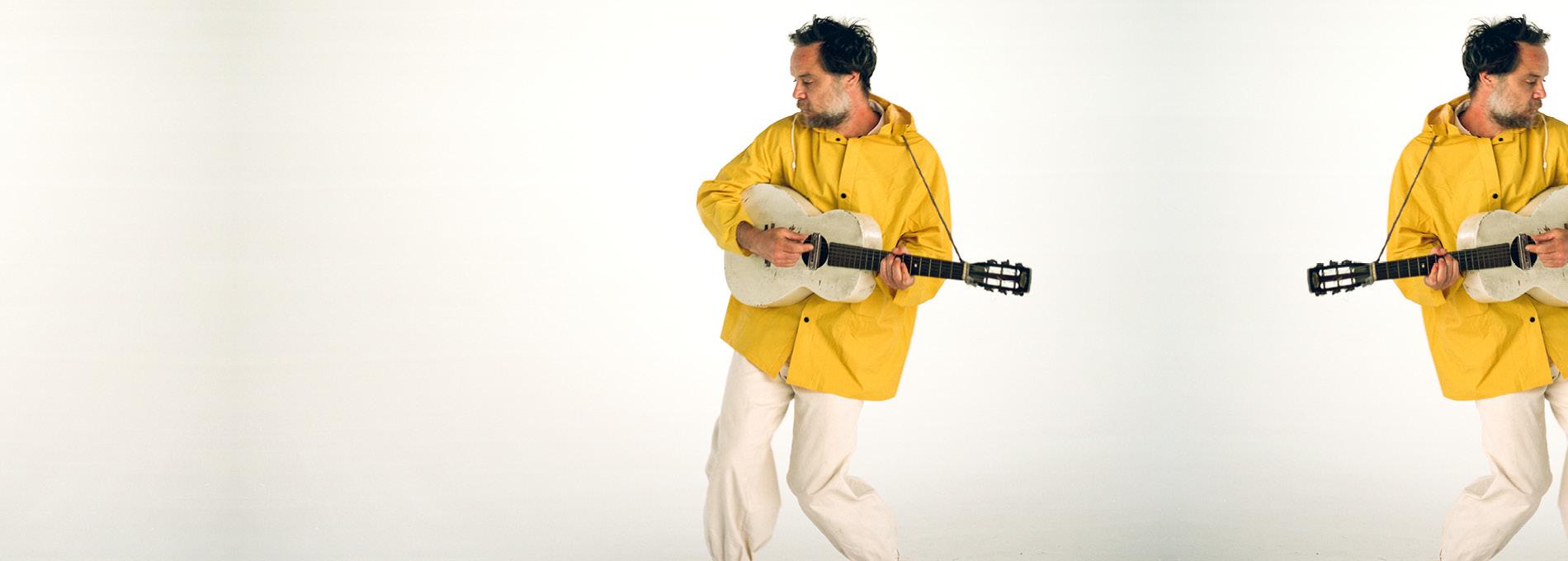 Rodrigo Amarante tocando violão branco