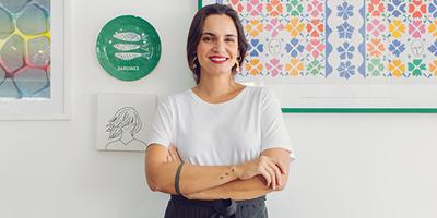 Renata Vanzetto Avental Braços Cruzados Parede branca com quadros