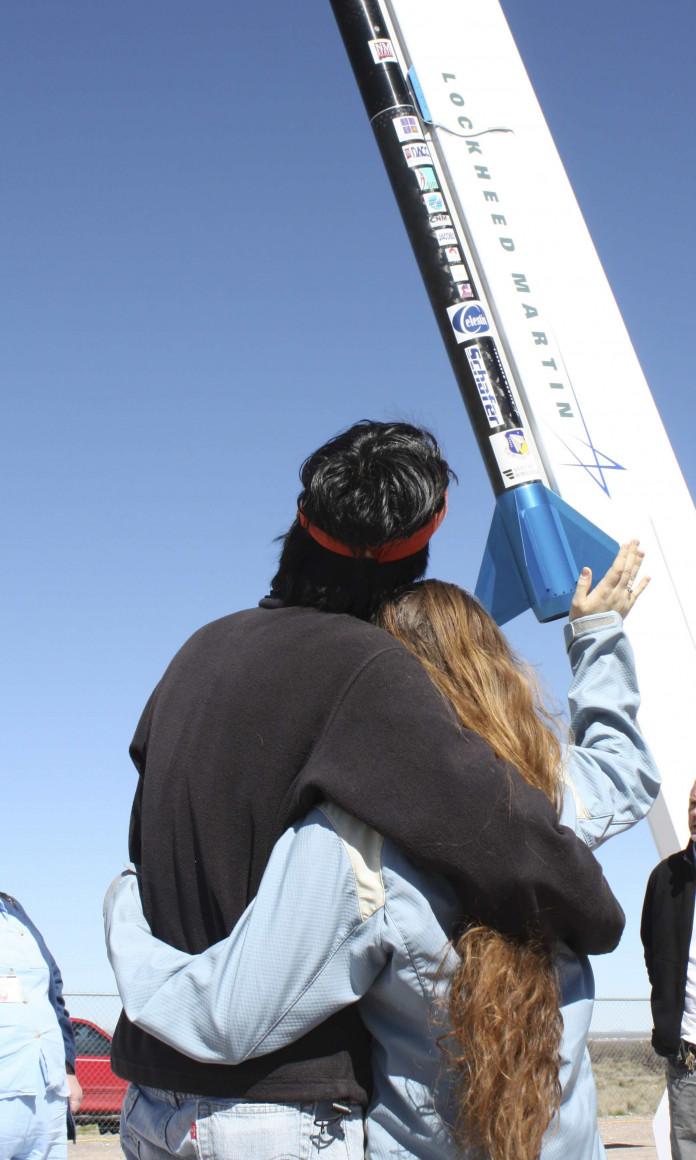 Casal abraçado acena para um foguete saindo do chão ao lado de uma bandeira dos Estados Unidos