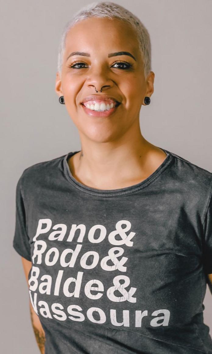 Mulher de cabelo curto e descolorido veste uma camiseta cinza com as palavras Pano & Rodo & Balde & Vassoura