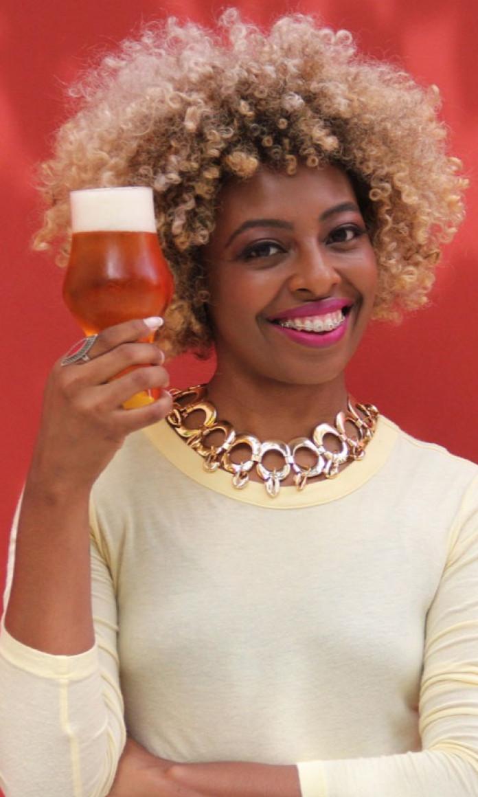 Mulher com cabelo black power loiro segura um copo de cerveja na frente do rosto