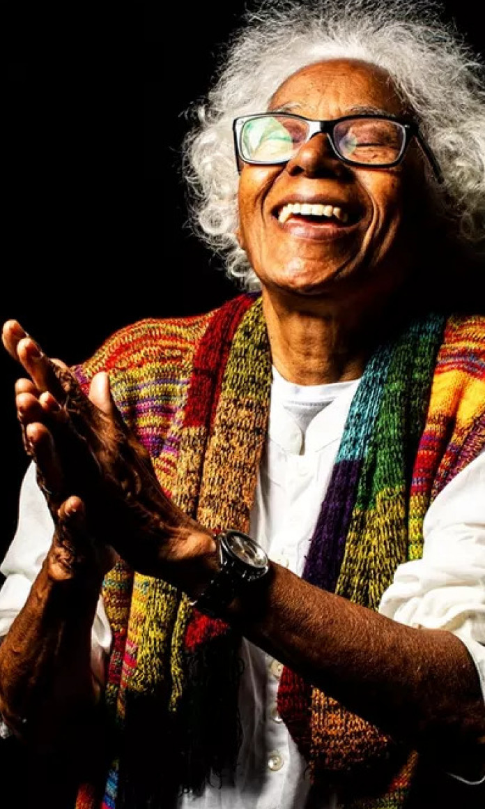 Mulher de cabelos brancos e óculos junta as palmas das mãos como em agradecimento enquanto olha para cima vestindo um lenço colorido