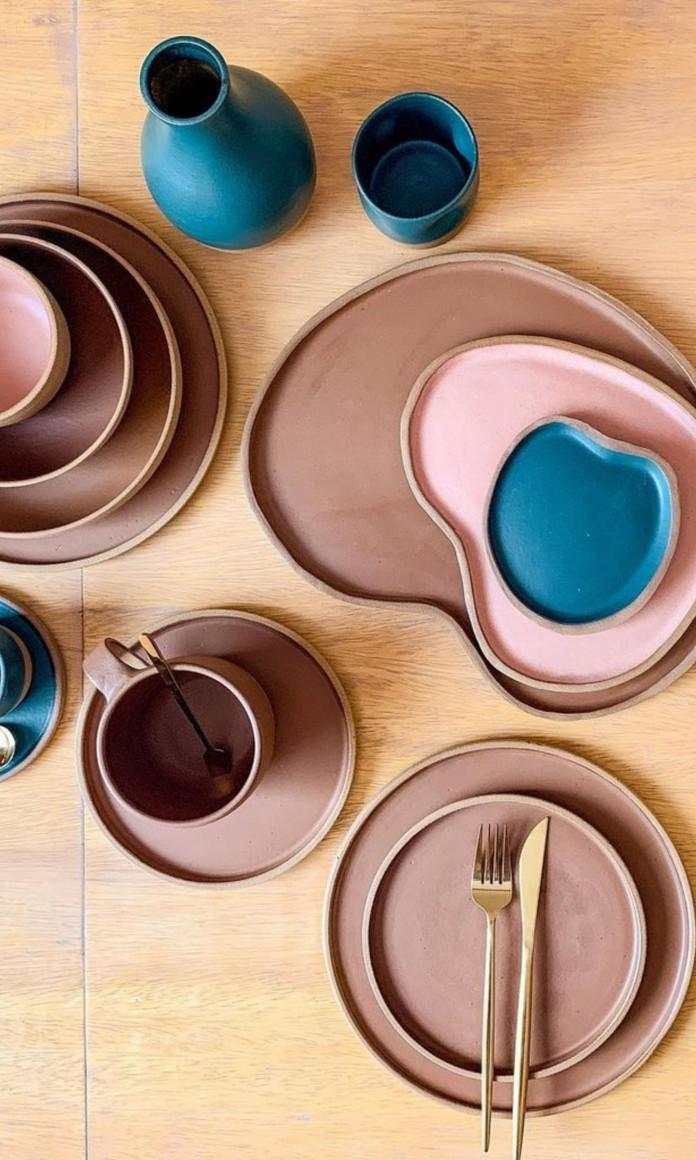 Ceramicas azuis e rosas de várias formas distribuidas sobre uma mesa