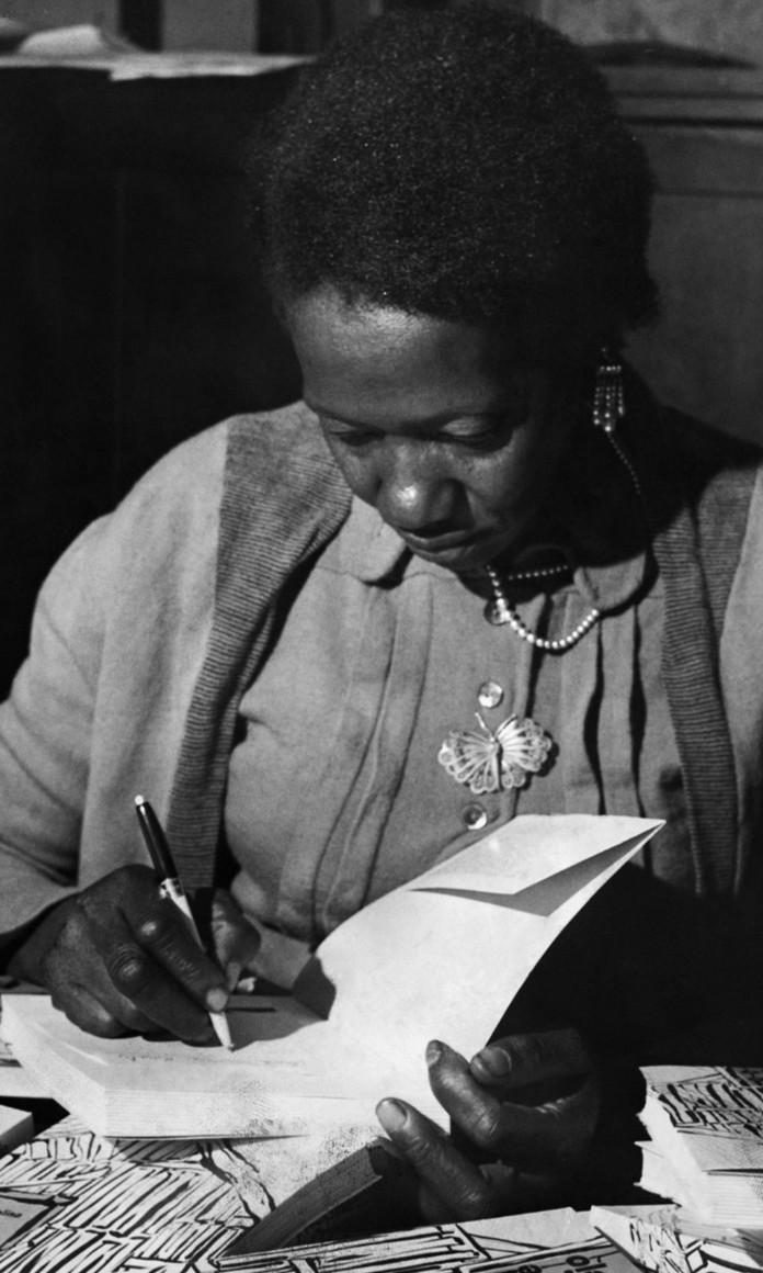 Mulher negra assina o livro que escreveu