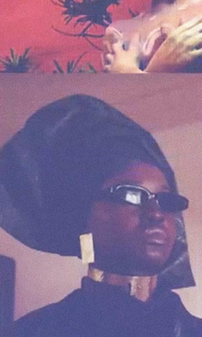 Mulher negra de oculos escuros, turbante preto e brincos e colar dourados