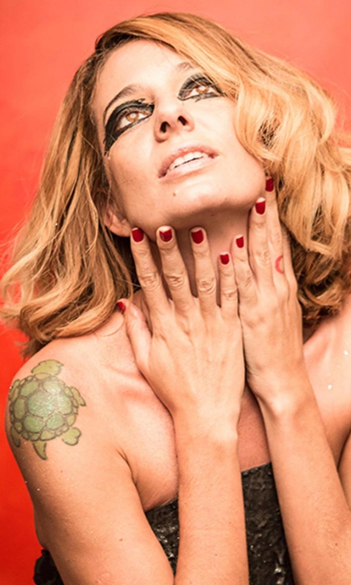 Cantora Letrux, mulher branca loira de cabelos médios, coloca as mãos de unhas pintadas de vermelho no queixo e tem os olhos com delineado preto